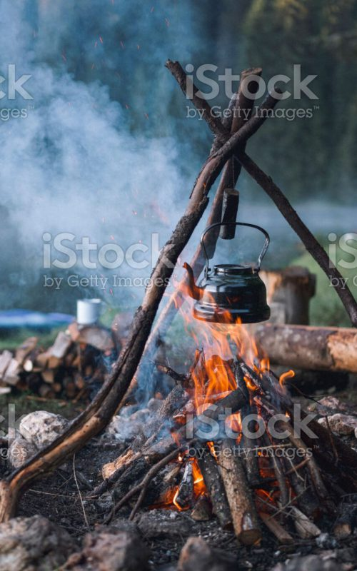 Vintage teapot with herbal tea at the campfire in the campsite next to the lake